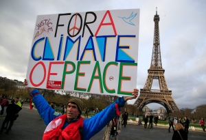An activist hold a poster during a demonstration near the Eiffel Tower, in Paris, Saturday, Dec.12, 2015 during the COP21, the United Nations Climate Change Conference. (AP / Thibault Camus)
