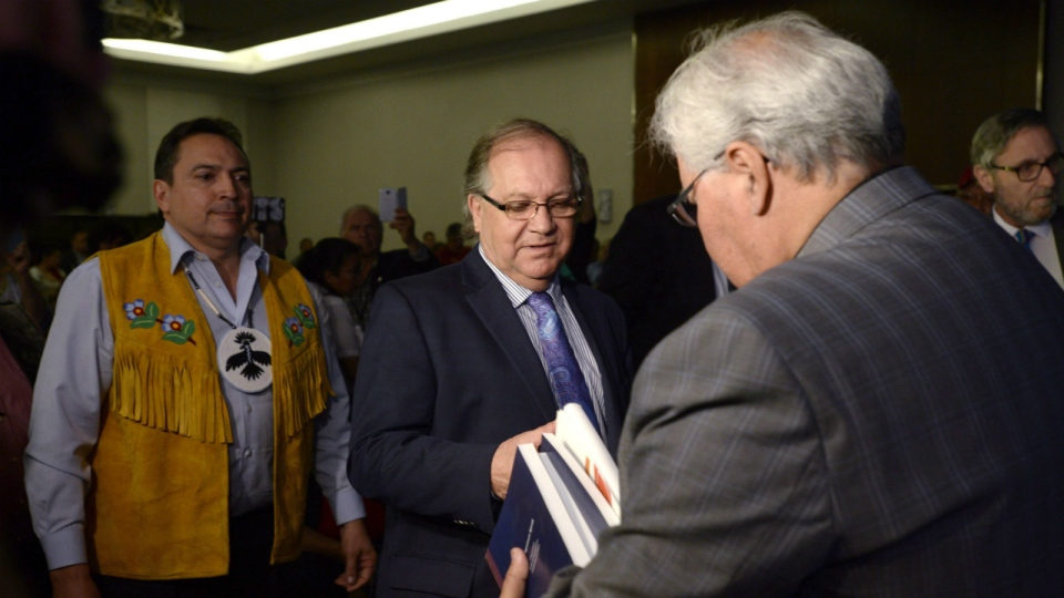 Commission Chairman Justice Murray Sinclair, right, hands a copy of the commission's report on Canada's residential school system to Aboriginal Affairs Minister Bernard Valcourt, centre, as Assembly of First Nations Nations Chief Perry Bellegarde looks on at the Truth and Reconciliation Commission, in Ottawa, on June 2, 2015. (Adrian Wyld / T HE CANADIAN PRESS)