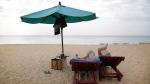 FILE - Tourists read on a beach in Khao Lak, Thailand, on Thursday, Dec. 25, 2014. (AP Photo/Wong Maye-E)