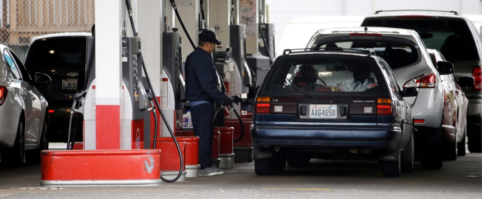 In this file photo, cars line up as an attendant pumps gas at a station in Portland, Ore., Wednesday, May 6, 2015. (AP/Don Ryan)