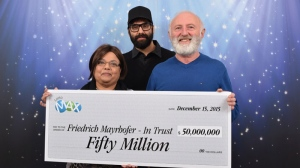 Friedrich and Annand Mayrhofer and their son Eric pose are awarded the $50 million, on Dec. 15, 2015. (BCLC Handout)