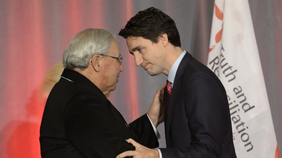 Prime Minister Justin Trudeau (right) greets Justice Murray Sinclair at the release of the Final Report of the Truth and Reconciliation Commission of Canada on the history of Canada's residential school system, in Ottawa on Tuesday, Dec. 15, 2015. (Adrian Wyld / THE CANADIAN PRESS)