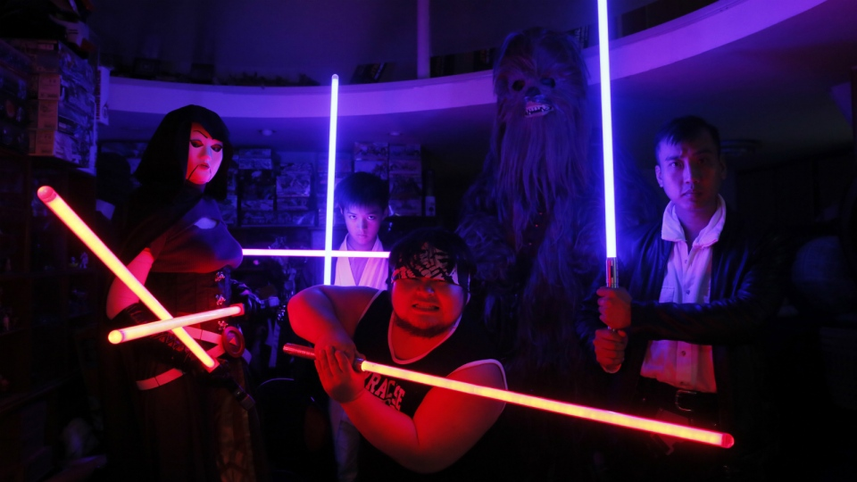 Tsai Jung-chou, centre, also known as 'Makoto Tsai', poses with friends as they wield his handcrafted replicas of the Star Wars lightsaber at his home workshop in New Taipei City, Taiwan on Dec. 14, 2015. (AP / Wally Santana)