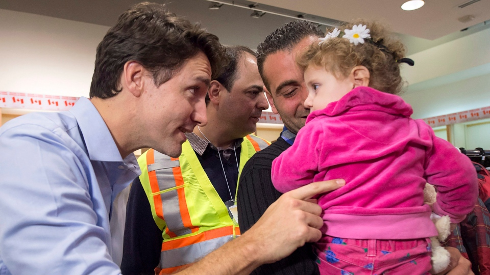 Prime Minister Justin Trudeau speaks with a young girl as he greets a family of Syrian refugees during their arrival at Pearson International airport, in Toronto, on Friday, Dec. 11, 2015. (Nathan Denette / THE CANADIAN PRESS)