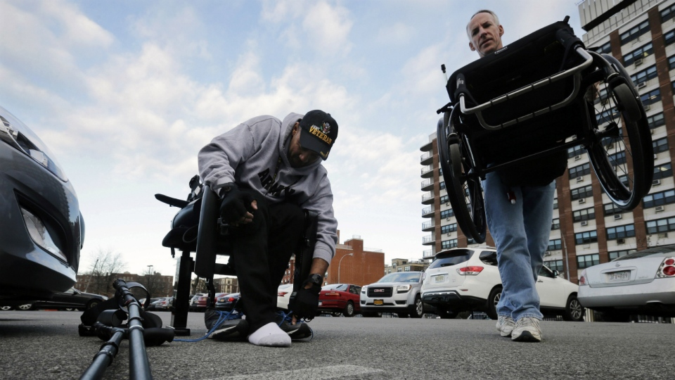 ReWalk Robotics service engineer Tom Coulter, right, moves paralyzed Army veteran Gene Laureano's wheelchair, as Laureano prepares to walk using a ReWalk device in Bronx, N.Y. on Wednesday, Dec. 16, 2015. (AP / Mel Evans)