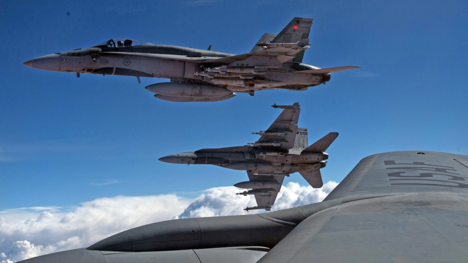 In this October 2014 photo provided by the U.S. Air Force, CF-18s are are refuelled over Iraq during a combat mission. (U.S. Air Force / Staff Sgt. Perry Aston)