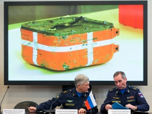 Russian aerospace forces Lt.-Gen. Sergei Dronov, left, and Lt.-Gen. Sergei Bainetov talk, as an image of a flight data recorder from the Russian warplane downed by Turkey is displayed on a screen in the background, during a news conference, in Moscow, Russia, Friday, Dec. 18, 2015. (AP Photo/Alexander Zemlianichenko)