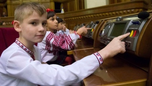 In this handout photo released by the Press Office of Ukrainian Parliament, a boy dressed in a traditional Ukrainian embroidered top presses the voting button at the Ukrainian parliament in Kiev, Ukraine, Friday, Dec. 18, 2015. (Press office of Ukrainian Parliament office handout photo via AP)