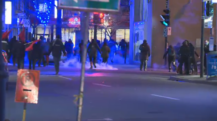 Protesters disperse as police fire tear gas in their direction during a protest in Montreal Dec. 18, 2015.