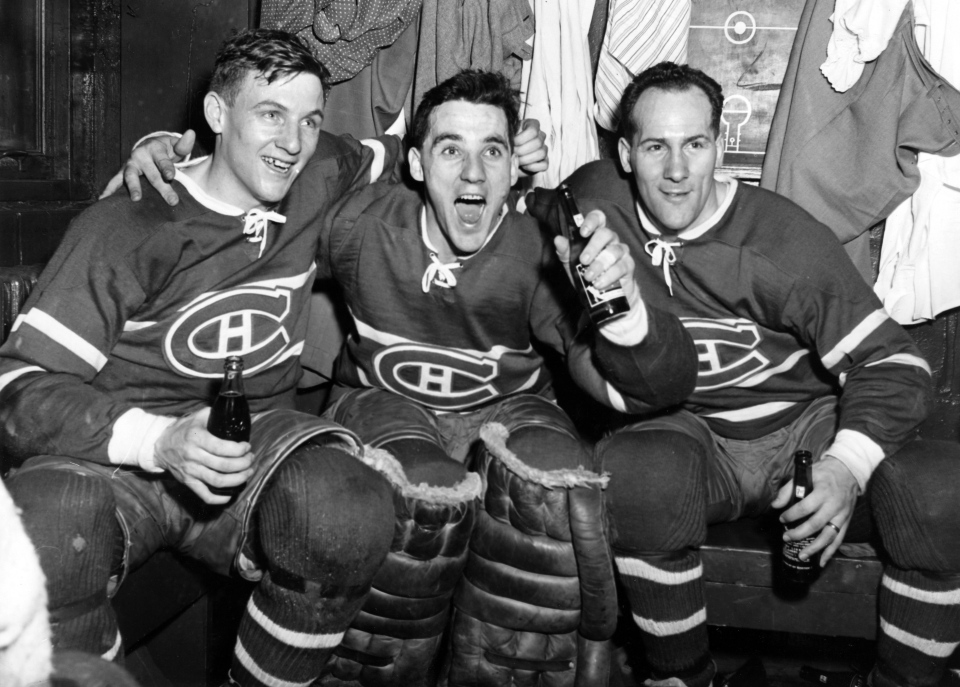 Montreal Canadiens' Dickie Moore, goaltender Jacques Plante and Floyd Curry celebrate in the dressing room after defeating the Boston Bruins 2-0 to sweep the semi-final playoff series on March 30, 1954. (The Canadian Press)