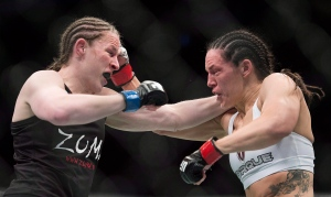 Alexis Davis, from Canada, right, trades blows with Sarah Kaufman, from Canada, during their UFC 186 bantamweight fight in Montreal on April 25, 2015. (Graham Hughes / The Canadian Press)