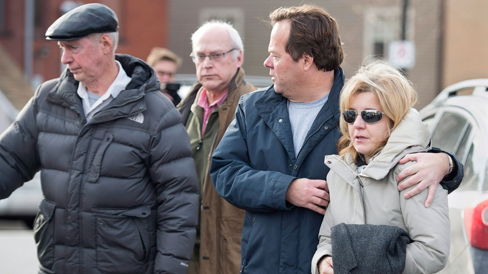 Lisa Oland, wife of Dennis Oland, carries her husband's coat from the Law Courts where he was found guilty of second degree murder in the death of his father, Richard Oland, in Saint John, N.B. on Saturday, Dec. 19, 2015. (Andrew Vaughan / THE CANADIAN PRESS)