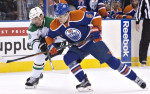 Dallas Stars' Patrick Sharp (18) and Edmonton Oilers' Mark Fayne (5) race for the puck during first period NHL action in Edmonton, Alta., on December 4, 2015. (Jason Franson / The Canadian Press)