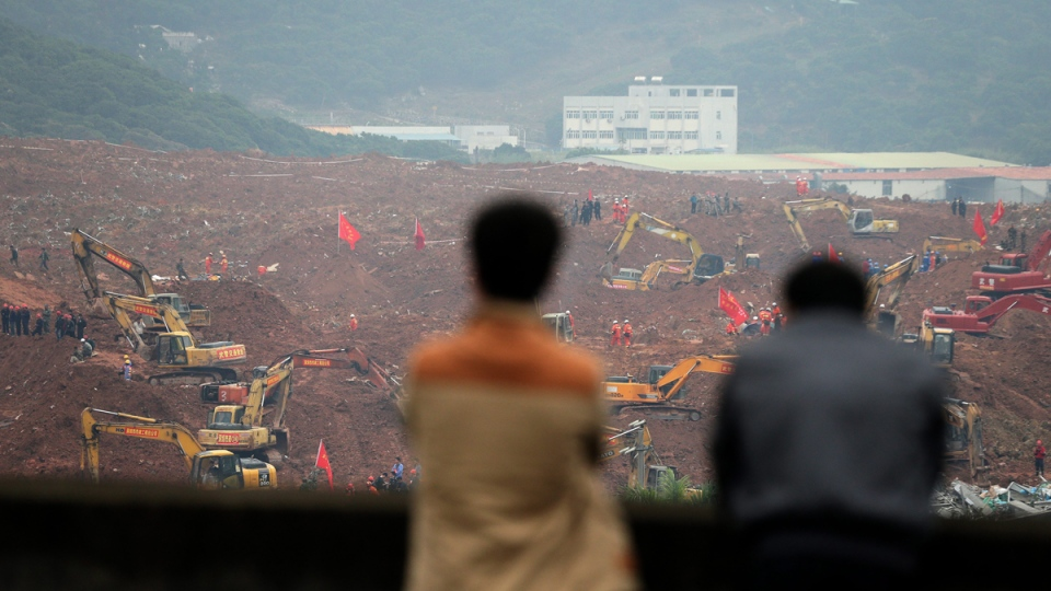 People watch rescuers using machinery to search for potential survivors following a landslide in Shenzhen, China, on Dec. 21, 2015. (Andy Wong / AP)