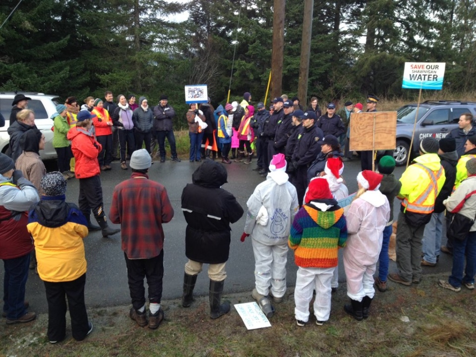 Dozens of protesters waving signs at RCMP members blocked trucks at the entry point of a contaminated soil dump at Shawnigan Lake, Tues., Dec. 22, 2015. (Twitter/@cwtheartist)