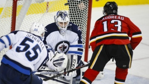 Winnipeg Jets goalie Michael Hutchinson, centre, lets in a hat trick goal from Calgary Flames' Johnny Gaudreau, right, during third period NHL hockey action in Calgary ON Tuesday, Dec. 22, 2015. (Jeff McIntosh / THE CANADIAN PRESS)