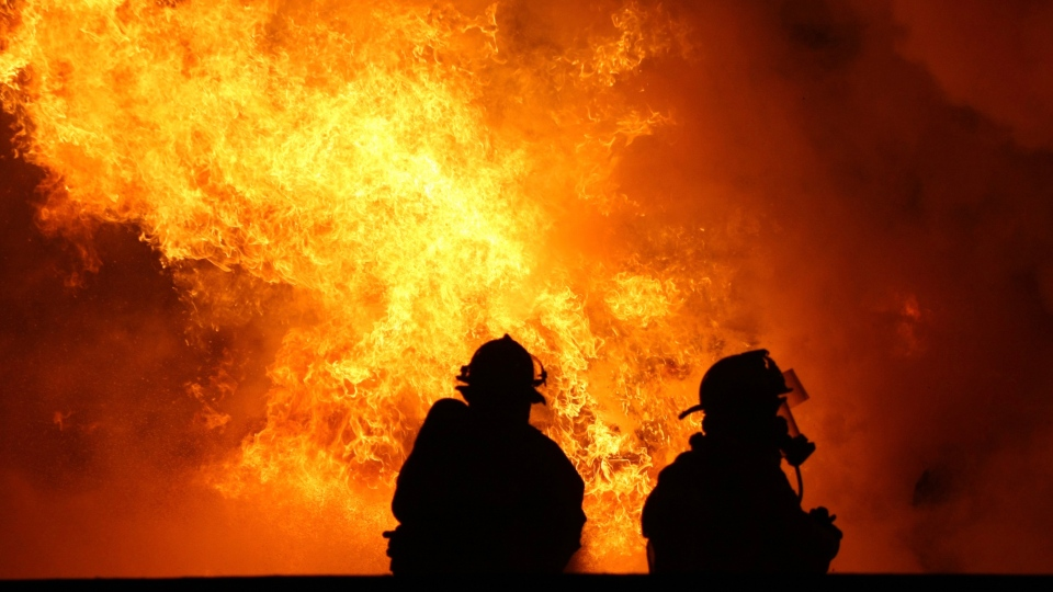 Firefighters work to put out a blaze on the Queen Elizabeth Way on Tuesday, Dec. 23, 2015. (Sam Fornasiero / MyNews)