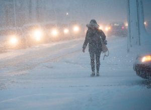 A pedestrian and traffic move slowly through the snow in Fredericton on Tuesday, December 15, 2015. (Stephen MacGillivray/THE CANADIAN PRESS)