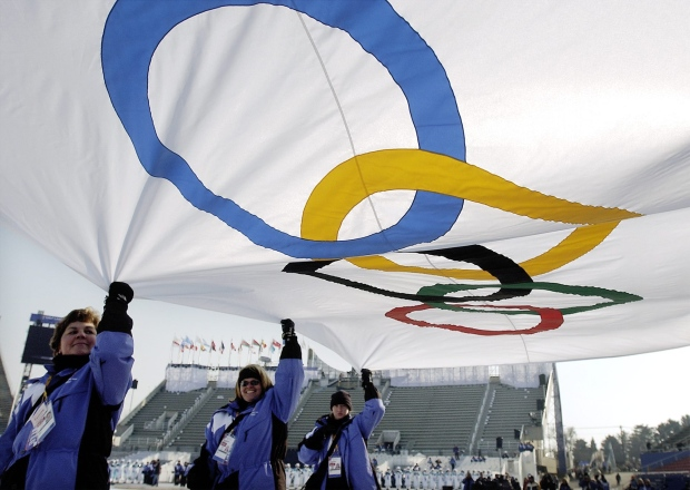 In this file photo, the Olympic flag is carried in during a rehearsal of the opening ceremony at Rice-Eccles Olympic Stadium on Monday, Feb. 4, 2002 in Salt Lake City. (AP/Laura Rauch)