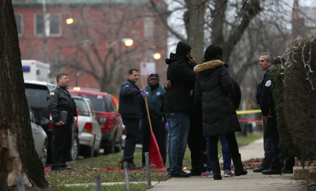 Chicago police officers talk with relatives of one of the two people killed by a police officer, as they investigate a shooting in the entry of their apartment in Chicago on Saturday, Dec. 26, 2015. (Abel Uribe / Chicago Tribune)