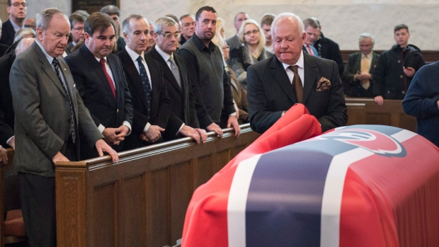 Former Montreal Canadiens' player Yvan Cournoyer removes the flag from the casket during funeral services for Canadiens' hockey legend Dickie Moore at the Mountainside United Church, in Montreal, on Monday, Dec. 28, 2015. THE CANADIAN PRESS/Paul Chiasson
