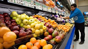 Grocery store owner Gilles Robin works on his fruits vegetable display in Breakeyville, Que. on Nov. 28 2006. (Jacques Boissinot / THE CANADIAN PRESS)