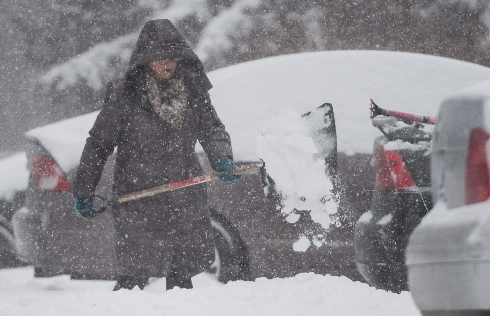 A woman shovels her driveway in the town of Hudson, west of Montreal, Tuesday, Dec. 29, 2015. (Graham Hughes / THE CANADIAN PRESS)