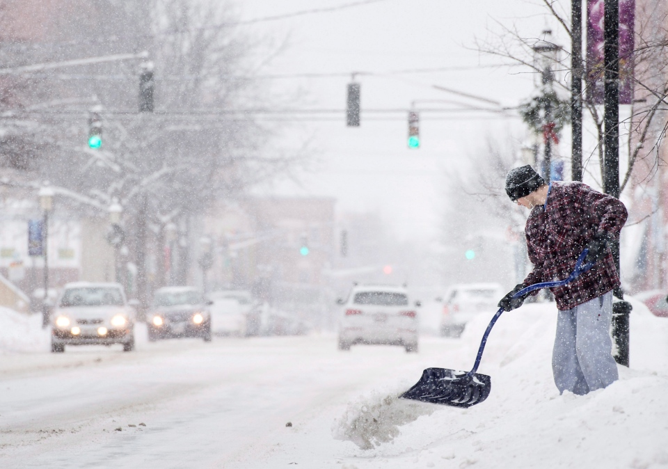 A man shovels snow during a winter storm in Fredericton, N.B. on Tuesday, Dec. 29, 2015. (Darren Calabrese / THE CANADIAN PRESS)