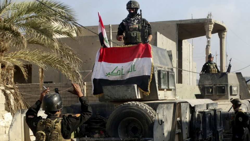 Smoke rises as Iraqi security forces attack the government complex in central Ramadi, 115 kilometres west of Baghdad, Iraq, Monday, Dec. 28, 2015. (AP / Osama Sami)