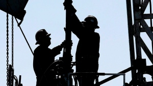 A service rig crew performs maintenance and repair work on an oilfield pumpjack and well head site near Halkirk, Alta., June 20, 2007. (THE CANADIAN PRESS/Larry MacDougal)