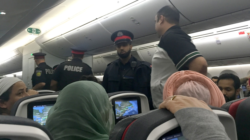 Police respond to an incident aboard a Toronto-to-India Air Canada flight, Wednesday, Dec. 30, 2015. (NOTE: The man standing in this photo was NOT the passenger that was arrested.)