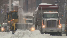 Snow removal trucks cart away snow in Montreal