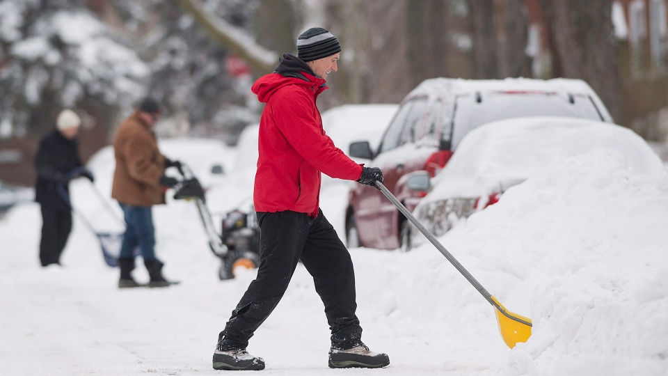People clear snow from around their cars in Montreal Wednesday, December 30, 2015 following the first major storm of winter in the region. THE CANADIAN PRESS/Graham Hughes