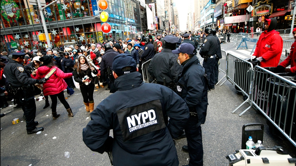 Counterterrorism officers, foreground, armed with an explosives detection device, far right, watch as other police officers inspect revelers entering a cordoned off area in Times Square in New York, on Dec. 31, 2014. (AP / Kathy Willens)