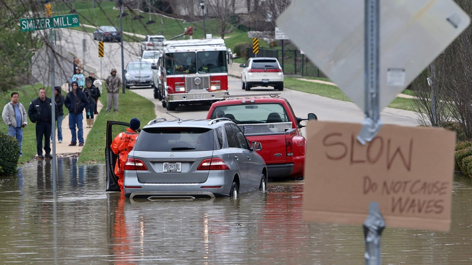 A Fenton firefighter puts a vehicle into neutral to remove it from floodwater in Fenton, Mo., Wednesday, Dec. 30, 2015. (J.B. Forbes / St. Louis Post-Dispatch via AP)