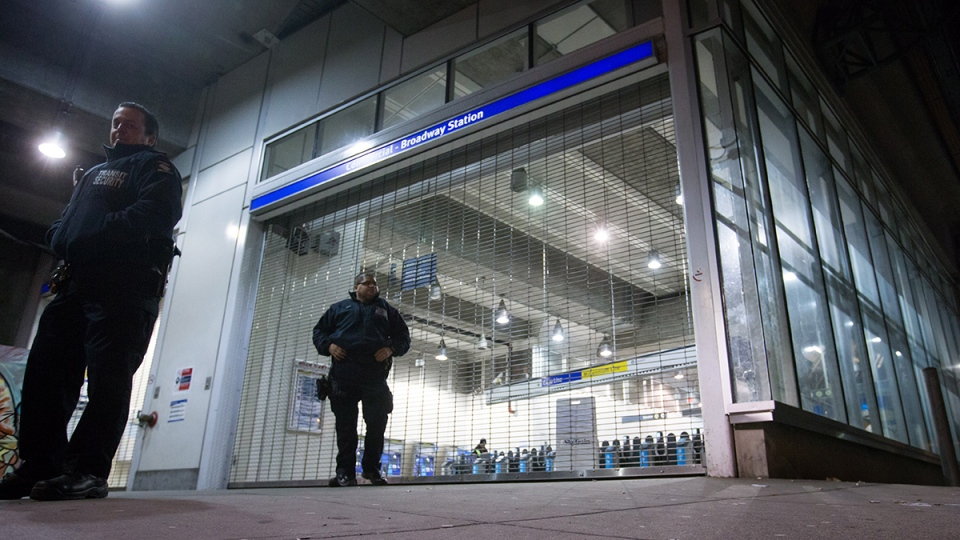 Transit security officers stand outside the Commercial-Broadway Skytrain station after the commuter train system was shut down to check for any possible damage to elevated guideways in Vancouver, in the early morning hours of Wednesday, Dec. 30, 2015. (Darryl Dyck / THE CANADIAN PRESS)