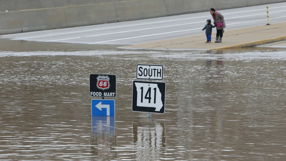 People look at floodwater from the Meramec River at the intersection of I-44 and Highway 141 in southwest St. Louis County, Wednesday, Dec. 30, 2015. (J.B. Forbes/St. Louis Post-Dispatch)