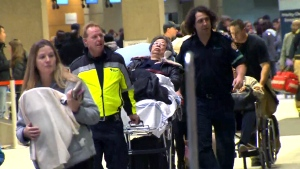 Emergency crews transport a passenger on a stretcher after an Air Canada flight was diverted to Calgary International Airport due to turbulence, in Calgary, Wednesday, Dec. 30, 2015.