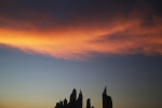 The setting sun sets wispy clouds aglow above the skyline of the Dubai Marina in Dubai, United Arab Emirates, on Wednesday, Dec. 30, 2015. (AP /Jon Gambrell)