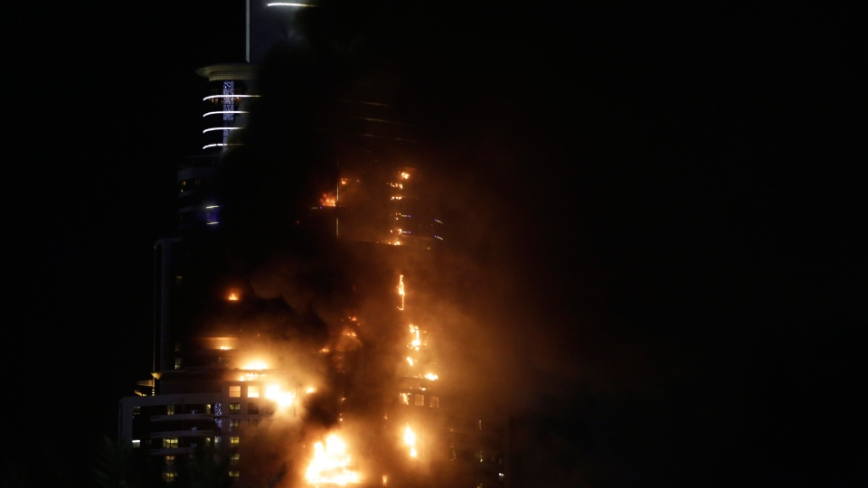 Smoke and flames pouring from a residential building, which also contains the Address Downtown Hotel, in Dubai, United Arab Emirates, Thursday evening, Dec. 31, 2015. (AP / Sunday Alamba)