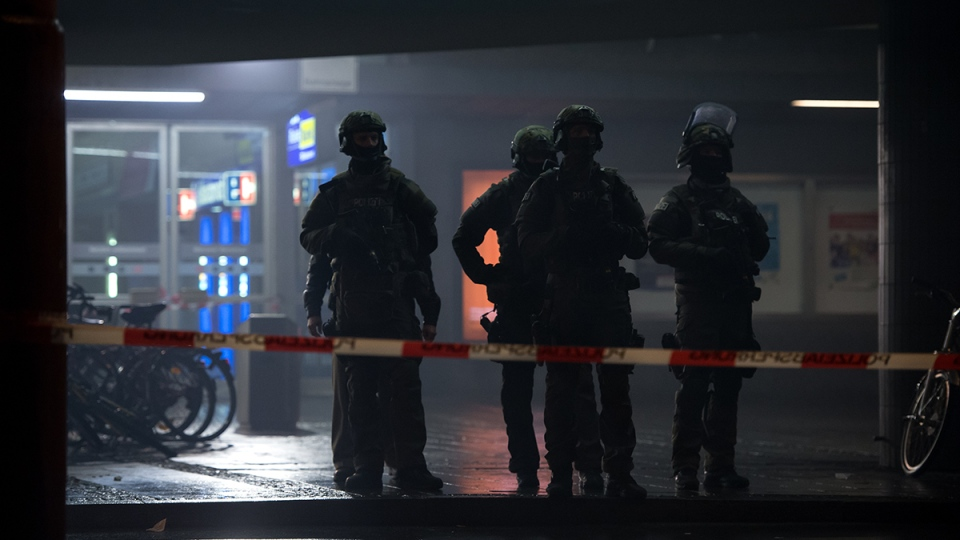 German special police stand in front of the Munich, southern Germany, main train station Thursday evening, Dec. 31, 2015. (Sven Hoppe / dpa via AP)