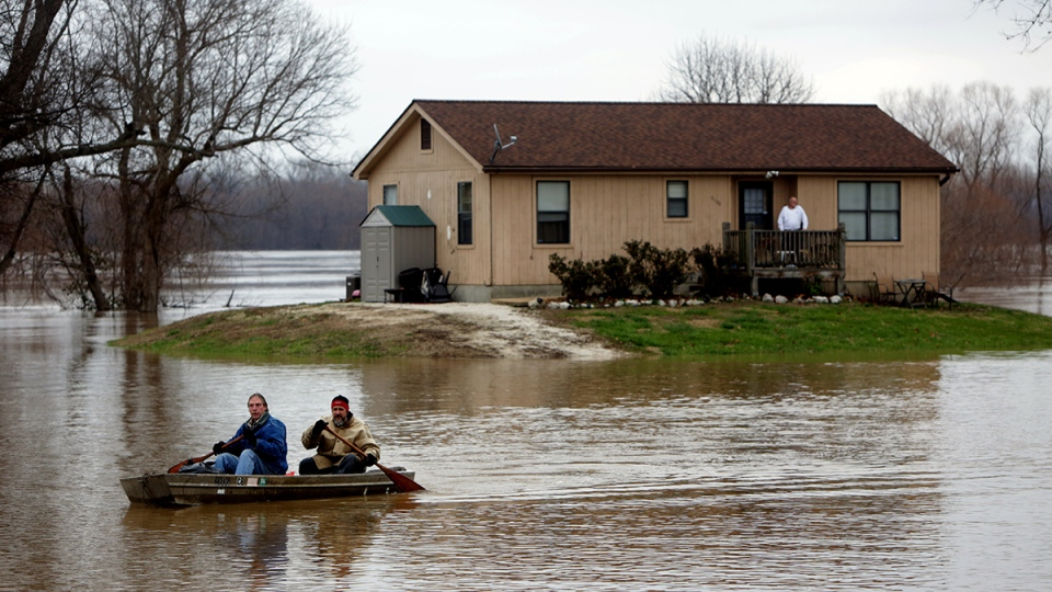 Scott Fox, front, who decided it was time to leave his residence on Mississippi Boulevard, which was surrounded by water, paddles a boat with his friend Tony Watkins in Kimmswick, Mo., Thursday, Dec. 31, 2015. (Laurie Skrivan / St. Louis Post-Dispatch via AP)