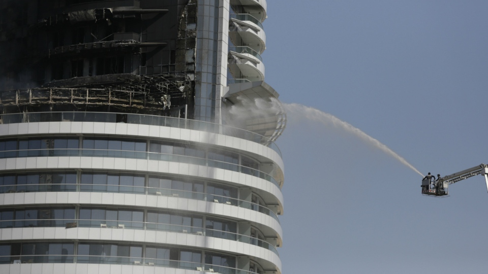 Firefighters spray water on a fire burning in the Address Downtown skyscraper in Dubai, United Arab Emirates on Friday, Jan. 1, 2016. (AP /Sunday Alamba)