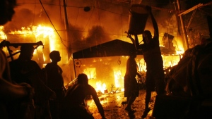 Residents help firemen battle a fire as Filipinos welcome the New Year at a poor neighbourhood of Tondo in Manila, Philippines Friday, Jan. 1, 2016. (AP / Linus Escandor II)