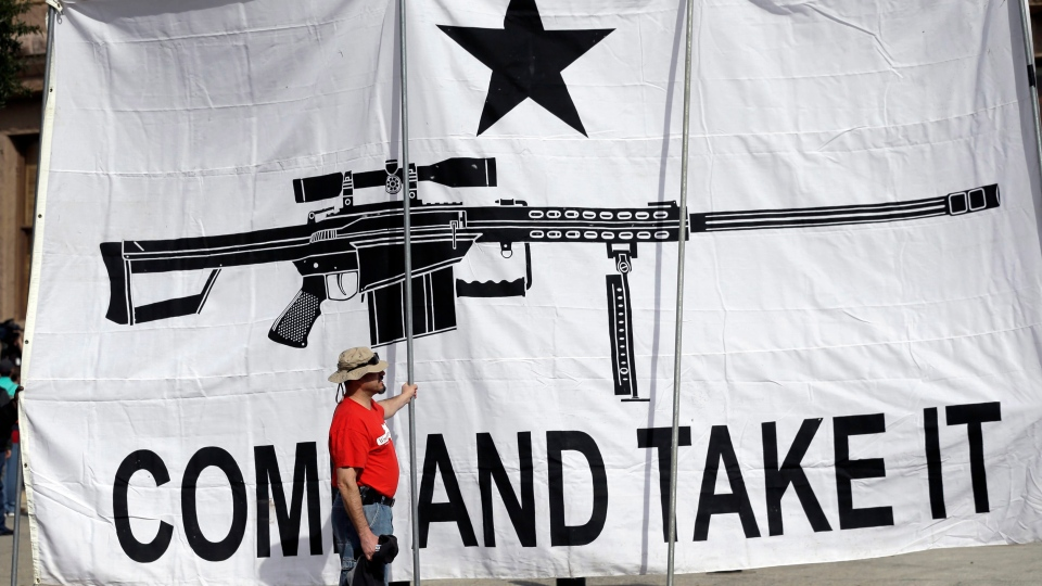 "A demonstrator helps hold a large ""Come and Take It"" banner at a rally in support of open carry gun laws at the Capitol, in Austin, Texas, Jan. 26, 2015. (Eric Gay/AP)"
