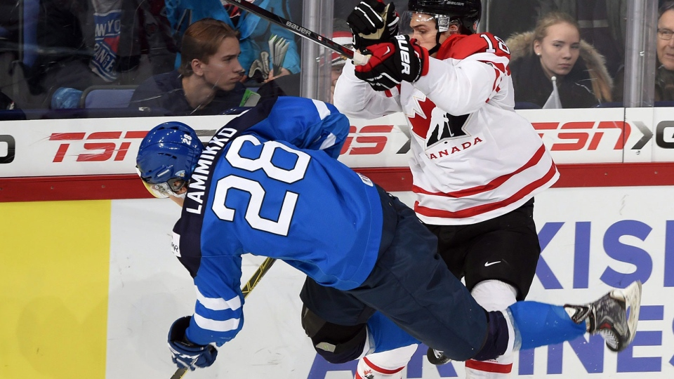 Canada's Jake Virtanen (18) tries to knock Finland's Juho Lammikko (28) off the puck during first period quarter-final hockey action at the IIHF World Junior Championship, in Helsinki, Finland, on Saturday, Jan. 2, 2016. (Sean Kilpatrick / THE CANADIAN PRESS)