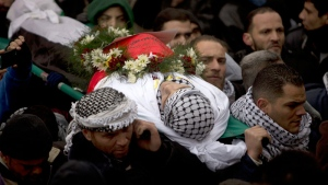 Palestinian mourners carry the body of Saad al-Atrash during the funeral of 17 Palestinians in the West Bank city of Hebron, Saturday, Jan. 2, 2016. (AP /Majdi Mohammed)