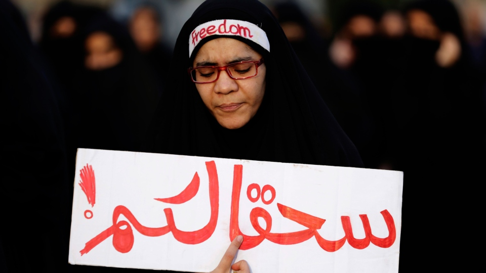 A Bahraini anti-government protester holds a banner in Arabic that reads 'damn you' during a demonstration against Saudi Arabia's execution of Shiite cleric Sheikh Nimr al-Nimr, in Daih, Bahrain, Saturday, Jan. 2, 2016.  (AP / Hasan Jamali)