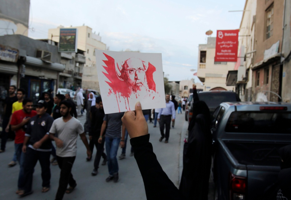 A Bahraini anti-government protester holds up a picture of Saudi Shiite cleric Sheikh Nimr al-Nimr, whose execution in Saudi Arabia was announced Saturday, during a peaceful demonstration in Daih, Bahrain, Saturday, Jan. 2, 2016. (AP/Hasan Jamali)