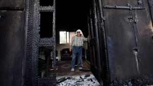 A Palestinian inspects a house after it was torched in a suspected attack by Jewish settlers, killing an 18-month-old Palestinian child and his parents, at Duma village near the West Bank city of Nablus. (AP / Majdi Mohammed)